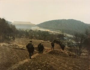 Picture of a Military troop crossing open country to a building in the far background