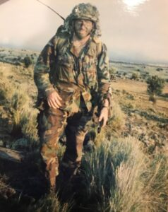 Picture of John Berry posing in Camo Military Uniform Hiking outdoors